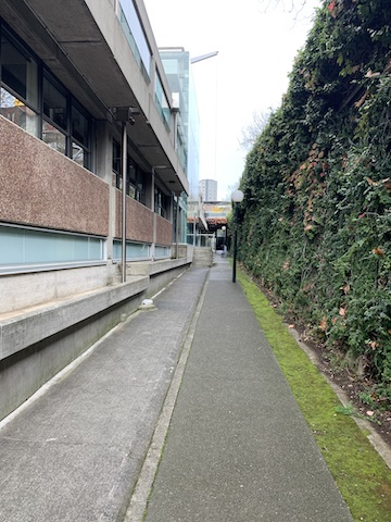 A deserted sunken walkway leading to an anonymous 1960's university building